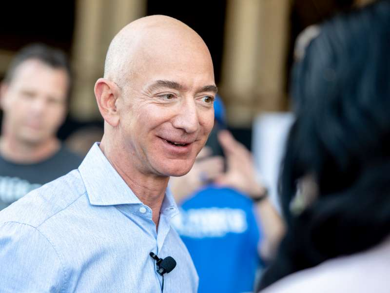 Jeff Bezos, founder and CEO of Amazon, speaks with employees after he made a surprise appearance during a Amazon Veterans Day celebration.