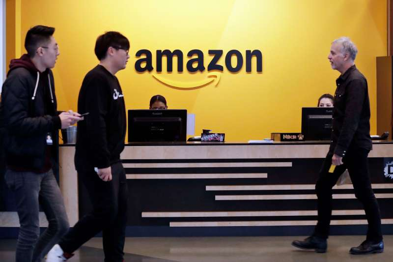 Employees walk through a lobby at Amazon's headquarters, in Seattle. Amazon, November 13, 2018.