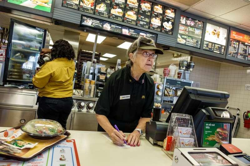 Senior woman working in McDonald's fast food restaurant (Photo by: Jeffrey Greenberg/UIG via Getty Images)