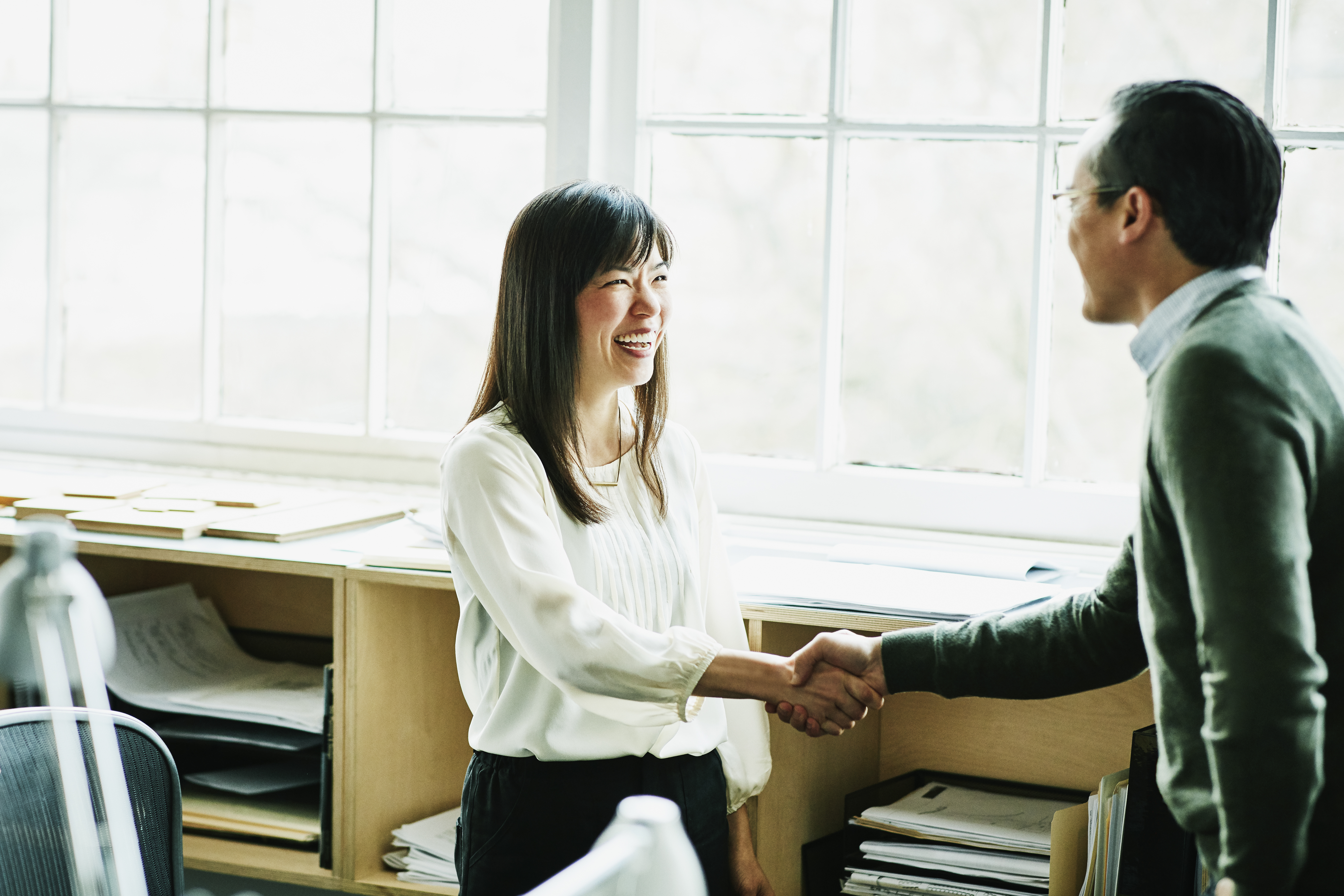 Smiling businesswoman shaking hands with client in design studio