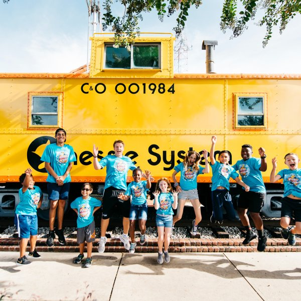 Children in matching shirts in front of bright yellow train caboose in Winter Garden, Florida