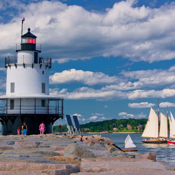 light house and sail boat off the coast of Portland, Maine