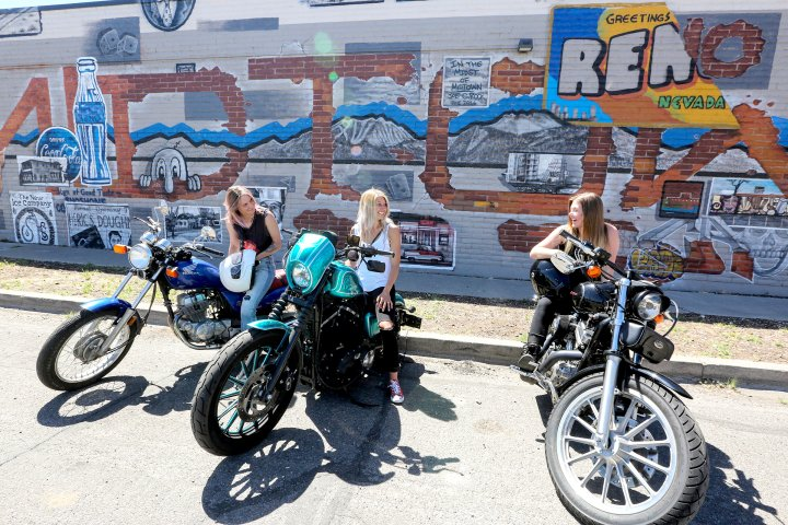 Three women on motorcycles in front of graffiti wall in Reno, Nevada
