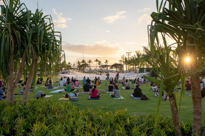 Crowd doing yoga in a park at sunset in Kakaako, Honolulu, Hawaii