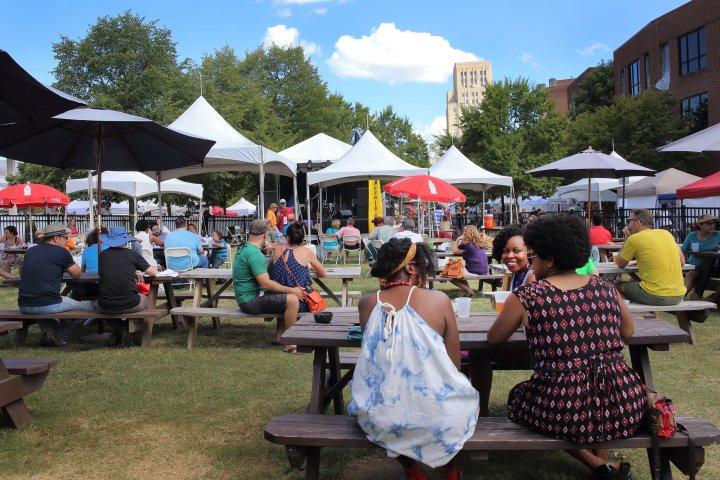 Crowd sitting at picnic benches at a park in Durham, North Carolina