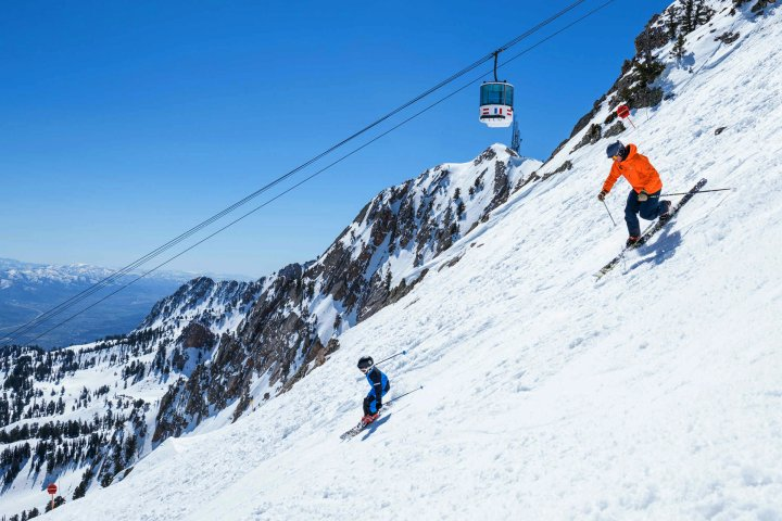 Parent and child skiing down a mountain in Layton, Utah