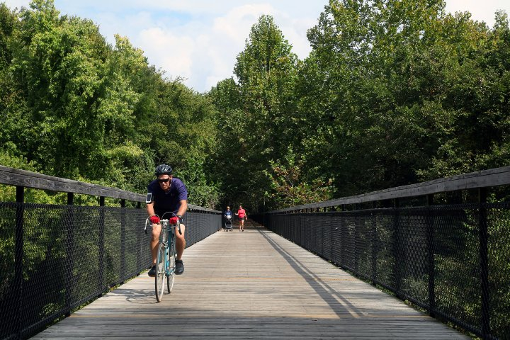 biker biking across bridge surrounded by trees in cordova, memphis, tennessee