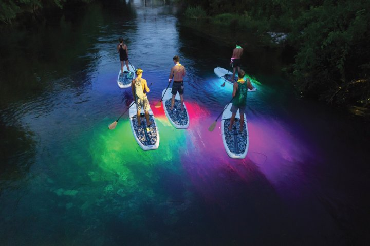 Three people on paddle boards in San Marcos, Texas