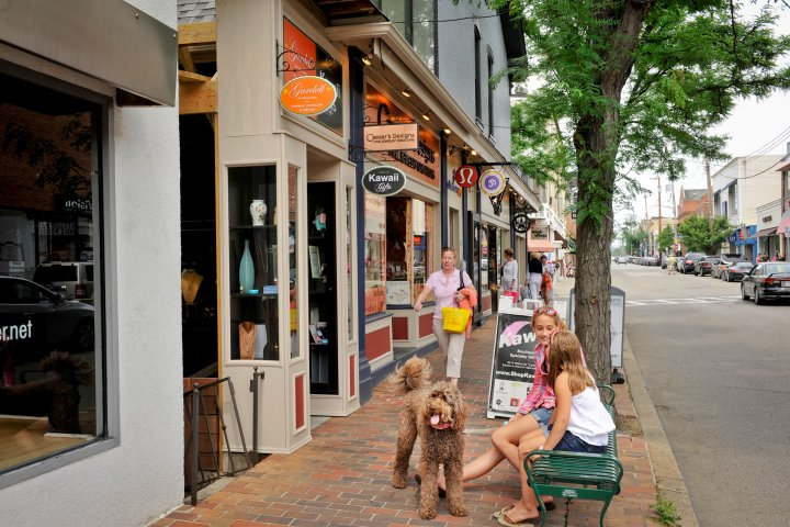 girls sitting with dog outside of a shop in Shadyside neighborhood in Pittsburgh, Pennsylvania