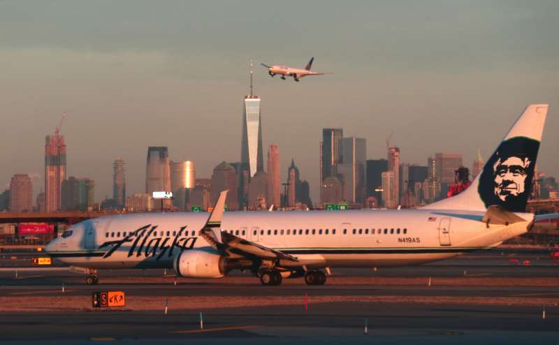 An Alaska Airlines airplane passes by the skyline of lower Manhattan in New York City as it heads to a gate at Newark Liberty Airport.