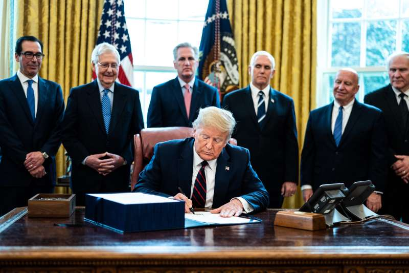 U.S. President Donald Trump signs the CARES Act in the Oval Office of the White House on March 27, 2020.