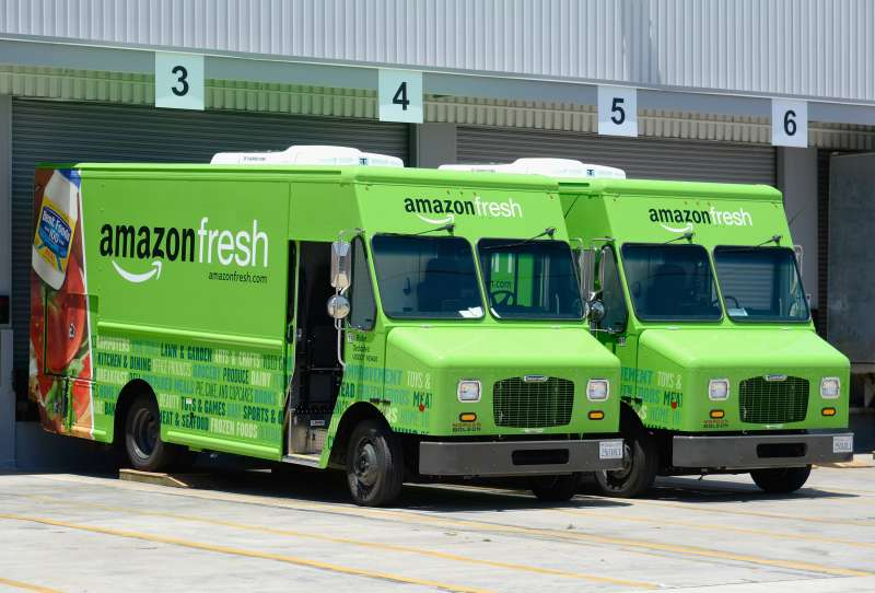 Amazon Fresh trucks sit parked at a warehouse in Inglewood, California.
