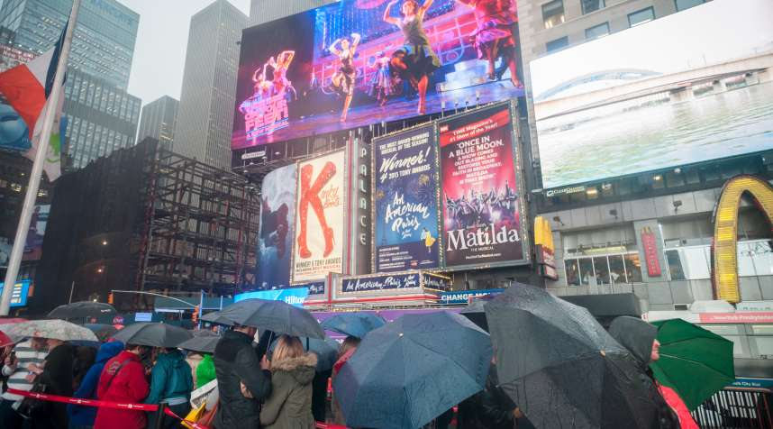 Visitors in the rain at the discount TKTS ticket booth in Times Square in New York.