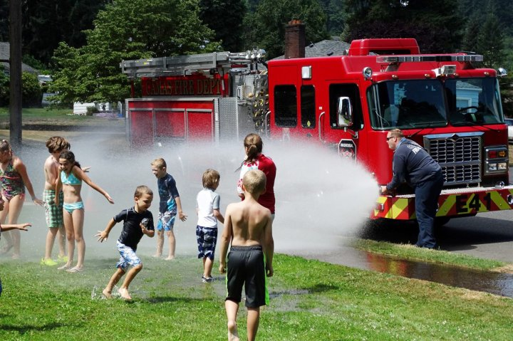 A group of kids play with the water from a fire truck in Camas Washington