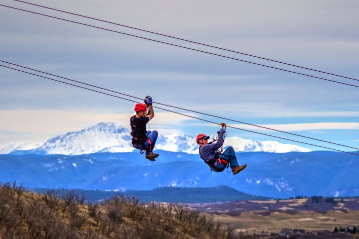 Two people zip-line with a beautiful view of Castle Rock Colorado in the background