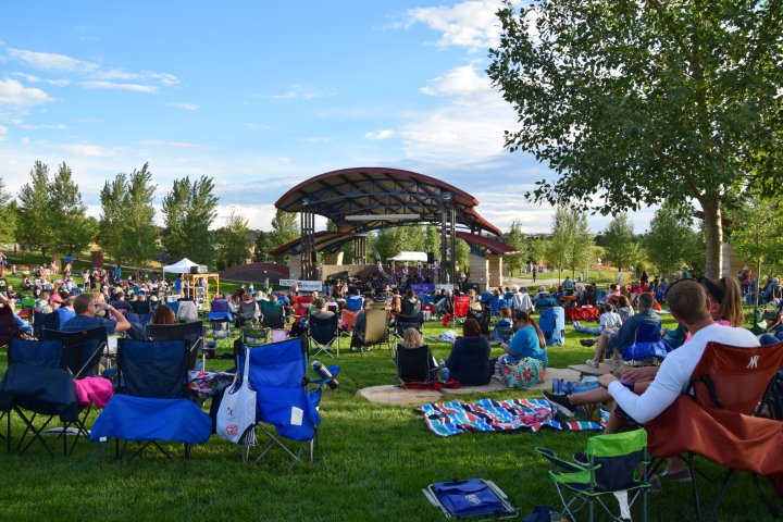 People enjoying the lawn at the local park and amphitheater in Centennial Colorado
