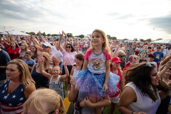 A girl in the crowd smiles of camera during a concert performance in Flower Mound Texas