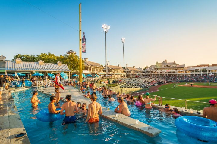A group of people watch a baseball game from inside a pool in Frisco Texas