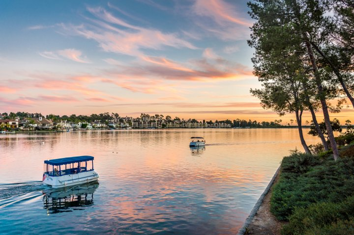 Two small passenger boats travel at sunset in Mission Viejo California