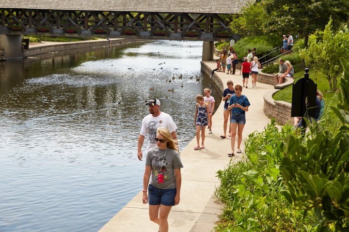 People walk along a river on a sunny day in Naperville Illinois