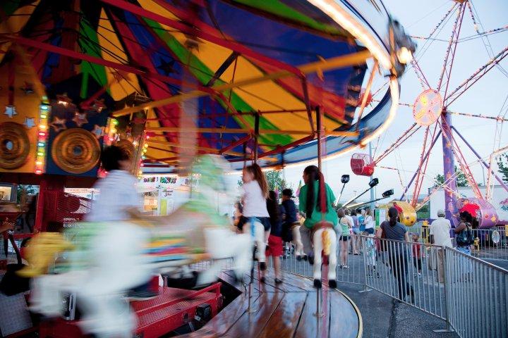 Kids enjoying a carrousel at a town fair in Overland Park, Kansas
