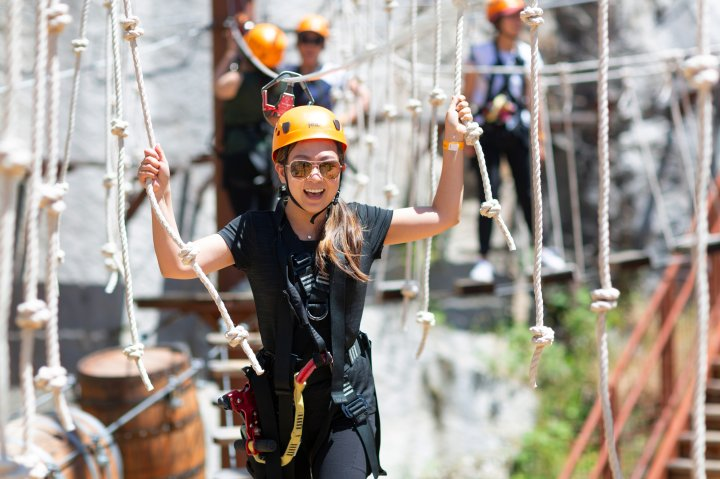 A young woman crosses a rope bridge at an adventure park in Rocklin California