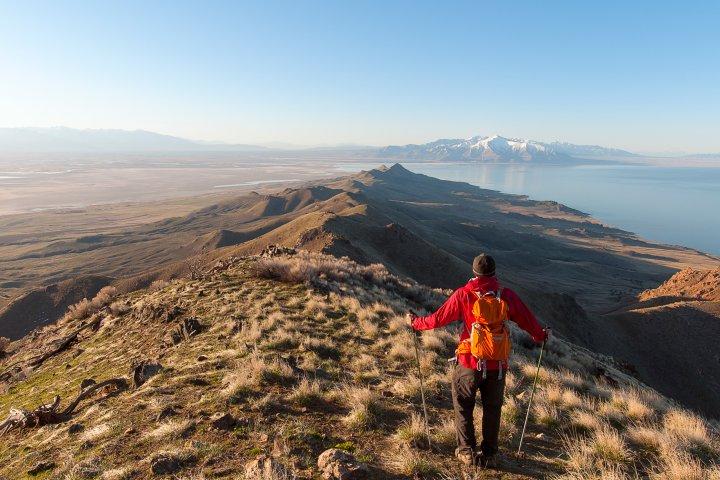 A hiker enjoys a beautiful mountain view in Syracuse Utah