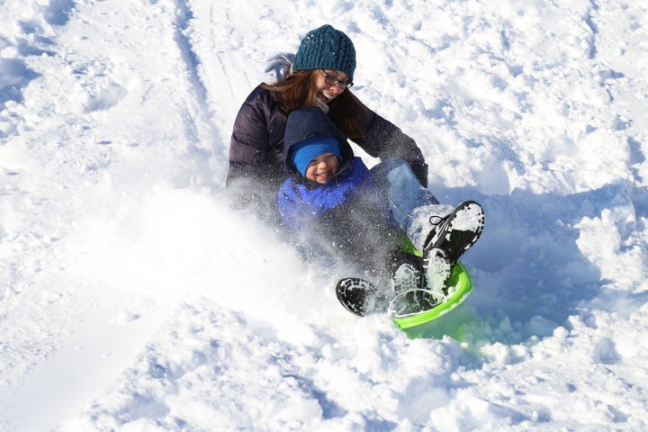A mother and her son sled down a hill full of snow in Waukee Iowa