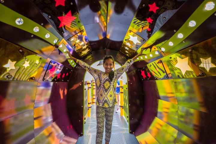 A girl smiles form inside a colorful playground tunnel in Woodbury, Minnesota